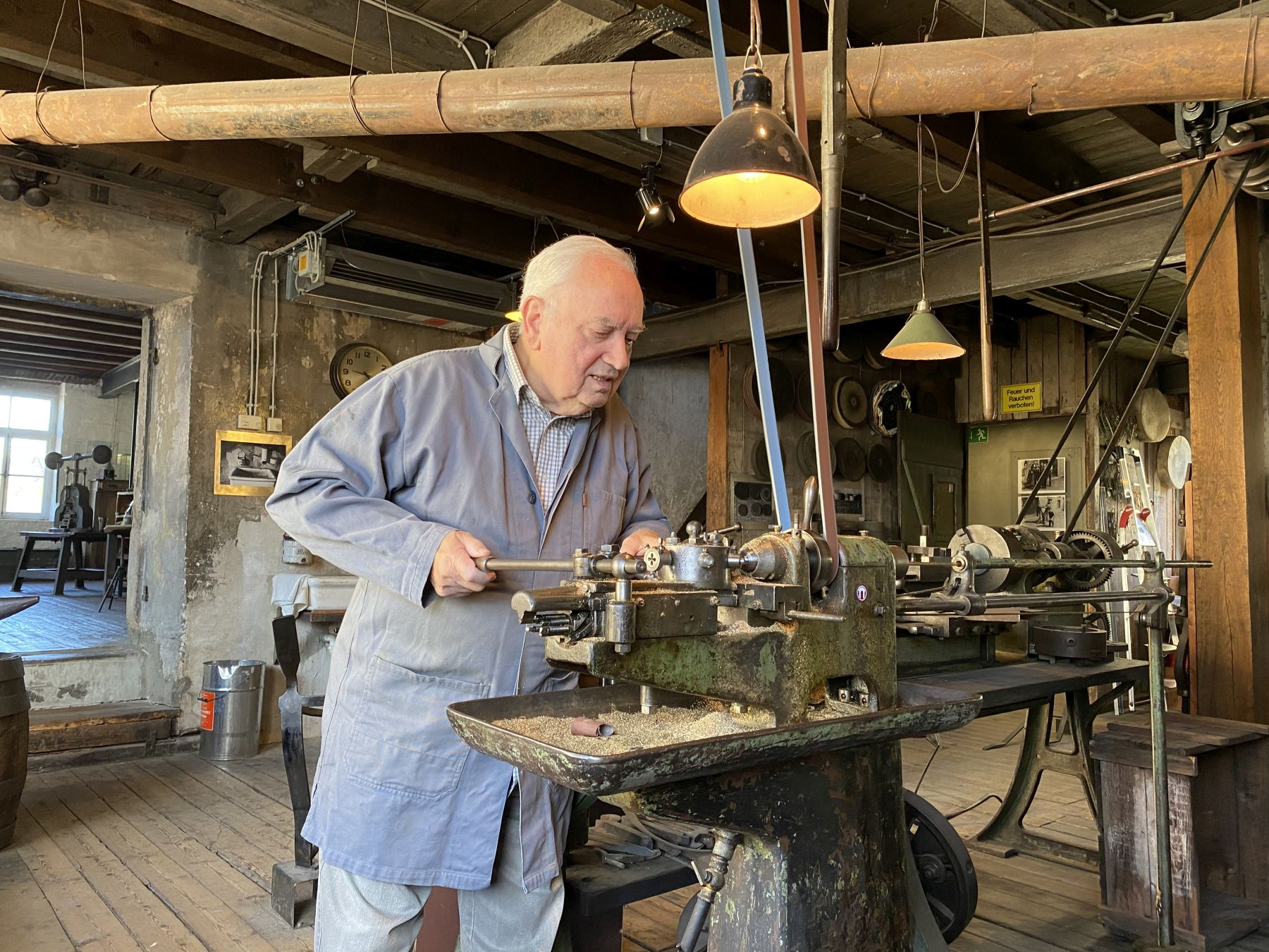 Dieses Foto zeigt einen Mann, der die Funktionsweise einer Maschine im Feinmechanischen Museum Fellenbergmühle vorführt.