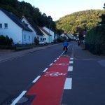 Zu sehen ist eine Straße mit neu aufgezeichnetem Radfahrerweg. Auf diesem fährt ein Radfahrer davon.