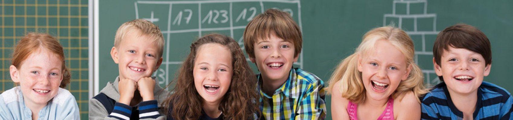 Auf dem Bild sind sechs lachende Kinder in der Schule zu sehen. Hinter hinter ihnen befindet sich eine Schultafel.