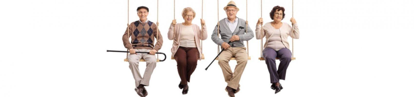 Auf dem Bild sind vier Senioren zu sehen. Diese sitzen auf Schaukeln und lachen.