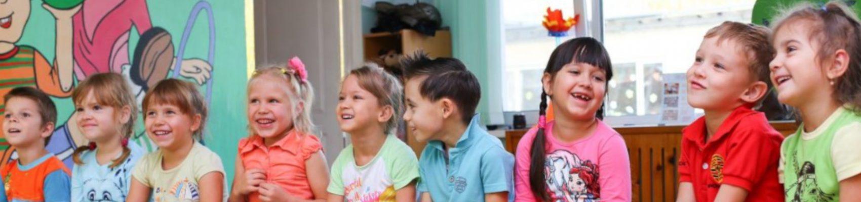 Auf dem Bild sind lachende Kinder zu sehen, die auf einer Bank sitzen.