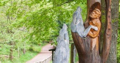 Das Bild zeigt den Eingang des Wolfsparks-Werner-Freund. Dort ist eine Holzskulptur zu sehen, die Werner Freund mit zwei Wölfen zeigt. Dahinter ist der Weg im Park und die grünen Bäume entlang des Wegs zu sehen.
