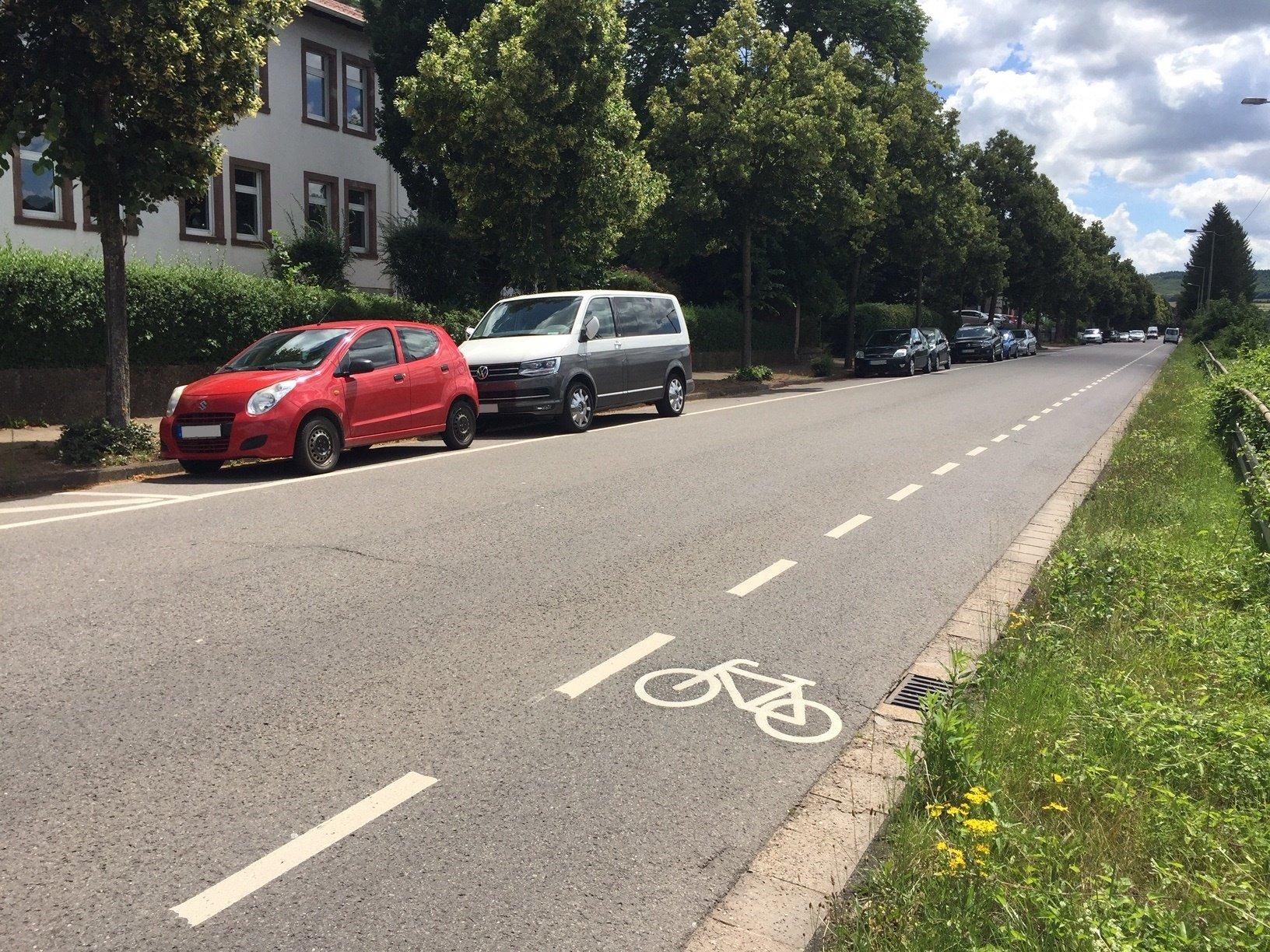 Das Bild zeigt den Radweg in der Saarbrücker Straße. Im Hintergrund sind zwei Autos zu sehen.