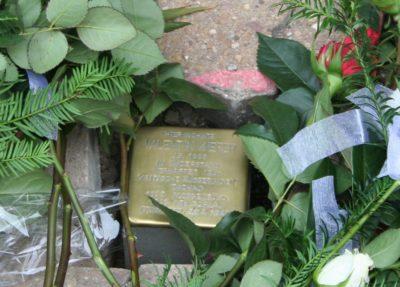Auf dem Bild ist der Stolperstein für Valentin Kiefer zu sehen, neben dem Rosen abgelegt wurden.