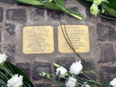 Auf dem Bild sind die Stolpersteine zur Erinnerung an Julius und Sara Frenkel zu sehen. Um die Steine wurden weiße Blumen abgelegt.