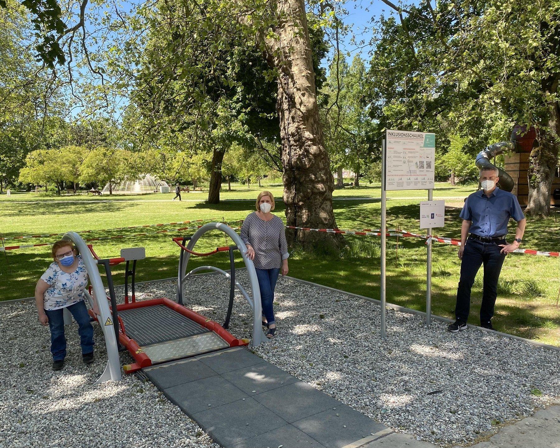 Auf dem Foto ist die Inklusionsschaukel im Stadtpark mit Bürgermeister Marcus Hoffeld, der Beauftragten für die Belange von Menschen mit Behinderung, Sarah Klemm, und der Vorsitzenden des Behindertenbeirates, Jessica Schwindling, zu sehen.