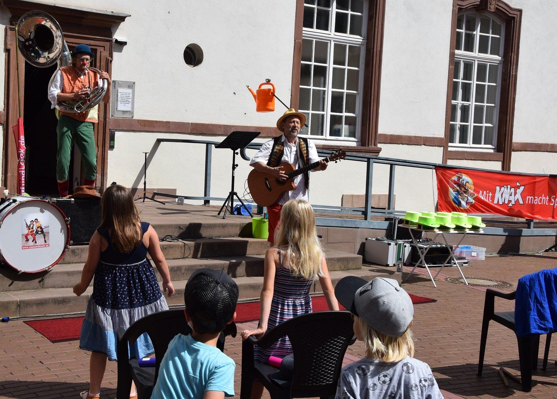 Das Bild zeigt Clown Lolek und Kinderliedermacher Casi bei ihrem Auftritt im Rahmen des Merziger Kindersommers 2021 vor dem Kinderpublikum im Innenhof des Rathauses.