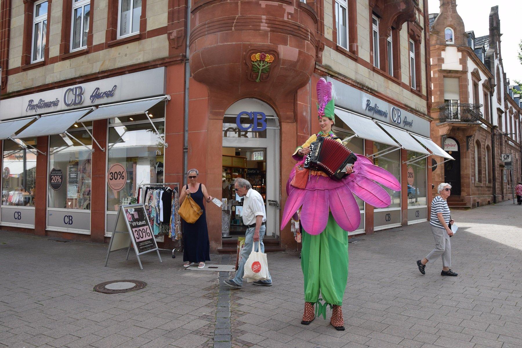 Das Bild zeigt die Darbietung von Stelzenläuferin Petra Raith mit Akkordeon beim Merziger Kleinkunstsommer 2021 in der Fußgängerzone. Petra Raith trägt ein lila-grünes Blumenkostüm und ist durch ihre Stelzen erhöht.