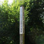 Das Bild zeigt einen Holzpfosten am Eingang des Parks der Andersdenkenden. Auf daran befestigten weißen Schildern ist rechts zu lesen: Möge Friede auf Erden sein. Links steht der gleiche Text auf luxemburgisch, der lautet: Fir datt de Fridden op der Welt regeiert.