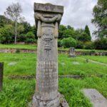 Das Bild zeigt die Gedenksäule für Alfred Kaufmann auf dem jüdischen Friedhof. Diese zeigt einen Äskulapstab und eine Inschrift.
