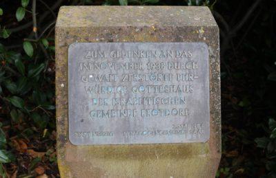 Das Foto zeigt den oberen Teil des Gedenksteins für die Brotdorfer Synagoge und die Metalltafel darauf.