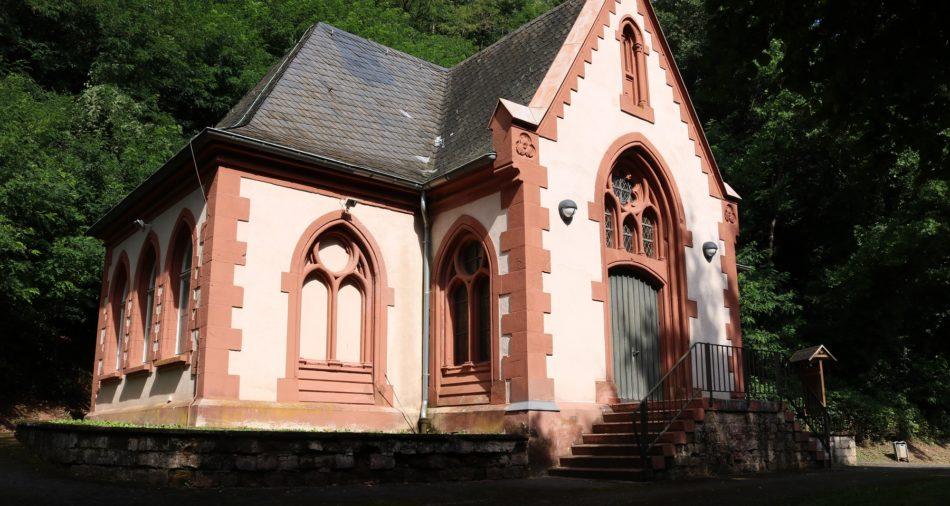 Das Bild zeigt das Haus am Münchberg im Park der Andersdenkenden. Das Haus ist weiß mit terrakottafarbenen Kanten.