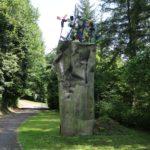 Das Bild zeigt die Metallskulptur Katterwahn im Park der Andersdenkenden. Die Skulptur besteht aus einer hohen, eingedellten Metallwanne. Darauf befinden sich Windräder.