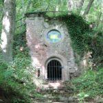 Das Bild zeigt ein kleines Gebäude im Park der Andersdenkenden. Oberhalb des kleinen Gittertors befindet sich ein rundes Fenster, in dem ein Lichtwellenauge von Lukas Kramer eingebracht ist. Auf dem Bild erscheint es wie ein gelbes Rechteck.