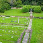 Das Foto zeigt den jüdischen Friedhof aus der Luftansicht. Im linken Bereich sind auf dem Gras Grabplatten und Grabstelen zu sehen. Im hinteren Bildbereich ist das säulenförmige Gedenkmal des Friedhofs zu sehen.