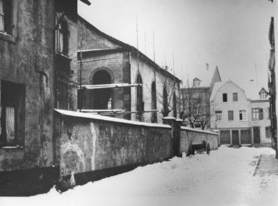 Dieses schwarz-weiß Bild zeigt eine Außenseite der Merziger Synagoge. Zu sehen ist die Mauer um das Gebäude und mehrere Fenster.