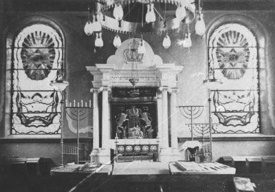 Dieses schwarz-weiß Bild zeigt den Innenraum der Merziger Synagoge. Zu sehen sind zwei Fenster, ein Kronleuchter und der Podiumsbereich.