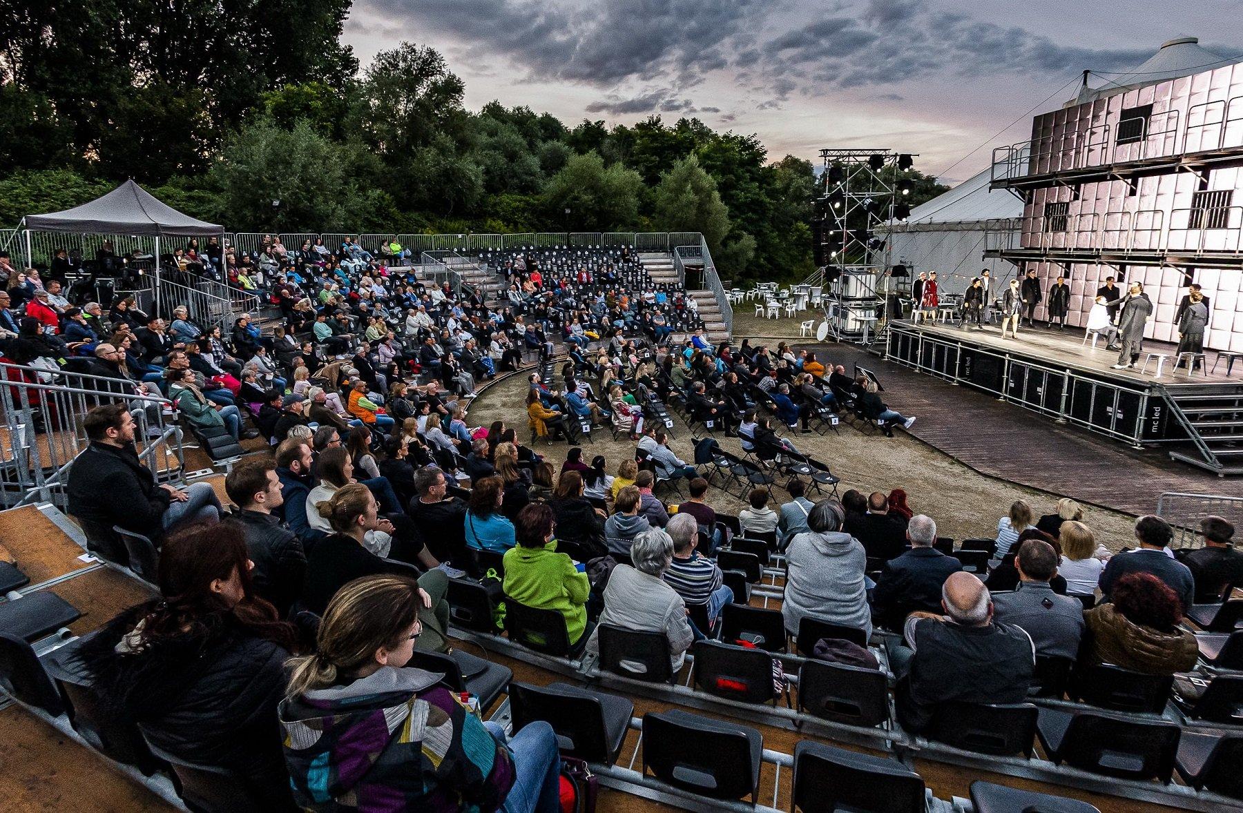 Das Bild zeigt die Perspektive des Publikums auf die Freiluftbühne bei der Aufführung des Musicals Jekyll and Hyde in der Freiluftarena Saar. Auf den Publikumsrängen sitzen viele Zuschauerinnen und Zuschauer und auf der Bühne ist das Ensemble beim Schauspiel zu sehen.
