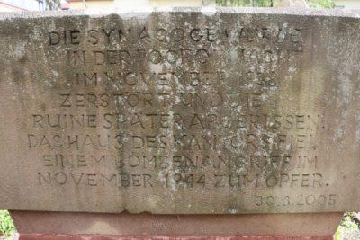Das Bild zeigt die Rückseite des Gedenksteins für die Merziger Synagoge. Als Inschrift ist darauf folgendes zu lesen: Die Synagoge wurde in der Pogromnacht im November 1938 zerstört und die Ruine später abgerissen. Das Haus des Kantors fiel einem Bombenangriff im November 1944 zum Opfer. 30.3.2005.
